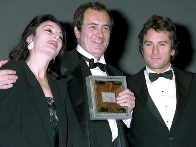 Italian movie director Bernardo Bertolucci, centre, flanked by actor Robert De Niro, right and actress Anouk Aimee, at the 40th Cannes Film Festival. Picture: AP Photo/Michel Lipchitz