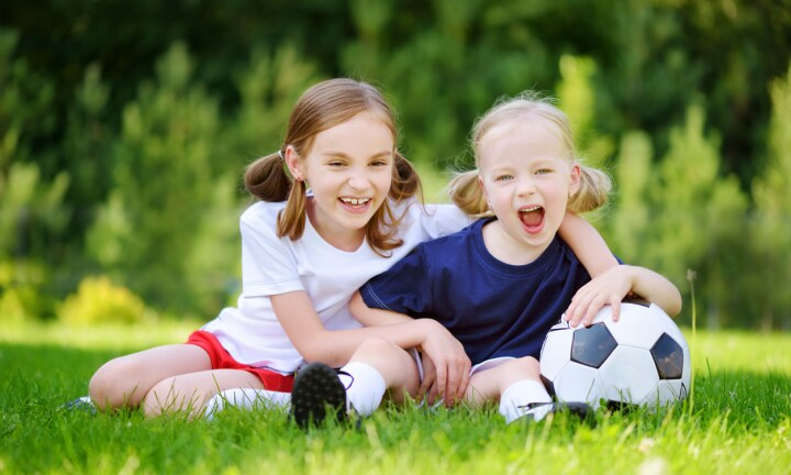Two cute little sisters having fun playing a soccer game on sunny summer day. Sport activities for children. Kids in sports uniform.