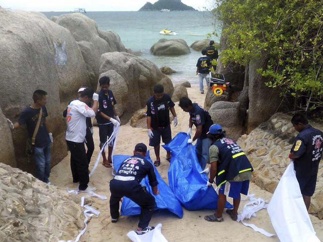 Thai rescue workers wrap the bodies of British tourists David William Miller and Hannah Victoria Witheridge who were found dead on a beach of Koh Tao island in September 2014.
