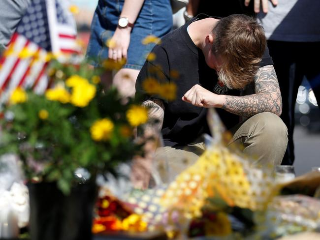 Bry Thompson pauses at a makeshift memorial in the middle of Las Vegas Boulevard following the mass shooting. Picture: Reuters