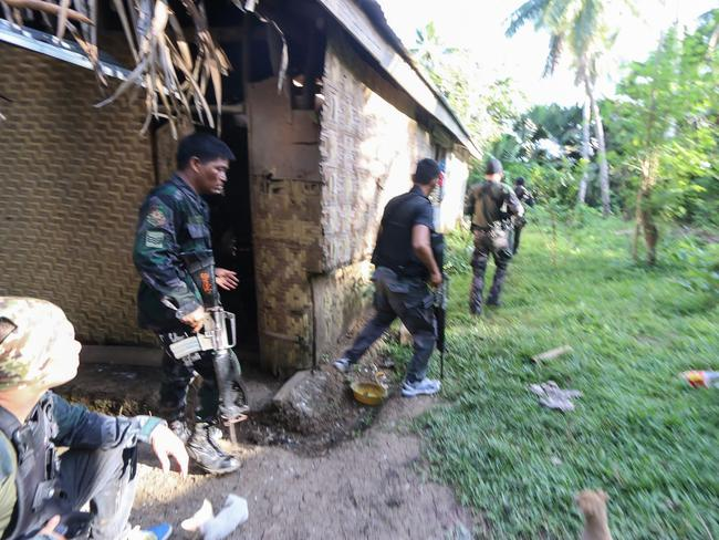 Police and soldiers take position as they engage with the Abu Sayyaf group in the village of Napo in Inabanga town, Bolo province, in the central Philippines on April 11. Picture: STR