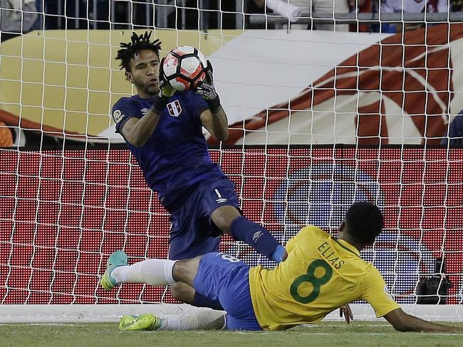 Peru's goalkeeper Pedro Gallese makes a save in front of Brazil's Elias (8) at the death.