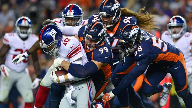 Quarterback Eli Manning #10 of the New York Giants is sacked by defensive end Gotsis.