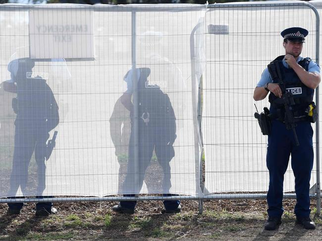 A police officer stands guard outside the burial ground where funerals for two victims are taking place today. Picture: William West/AFP