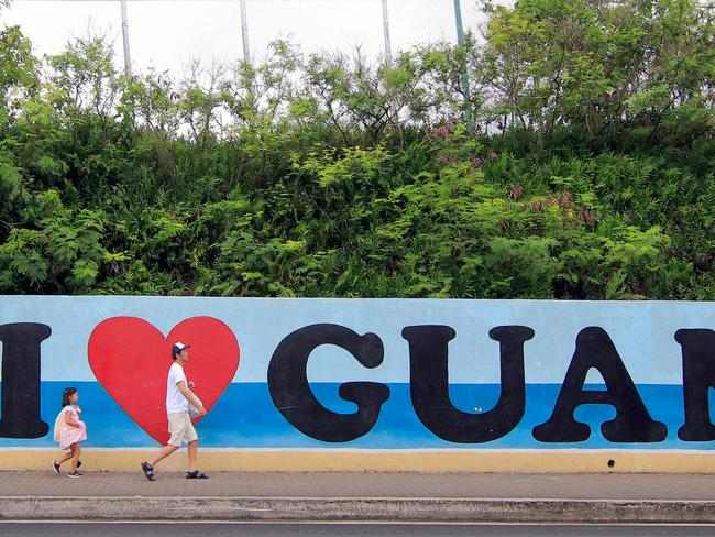 "Tourists walk past a wall painted with the slogan ""I love Guam"" in the Tumon district on the island of Guam. Picture: AFP PHOTO / Virgilio VALENCIA"