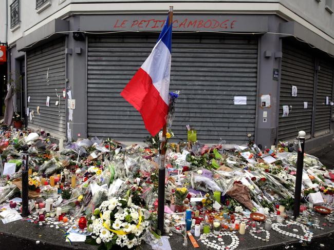 The French national flag, candles and flowers at a makeshift memorial in front of the Le Petit Cambodge restaurant in Paris in tribute to the victims of the attacks that killed at least 129 people and left more than 350 injured. Picture: Kenzo Tribouillard/AFP