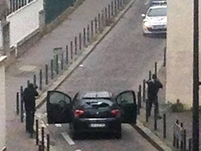 Escaped ... armed gunmen face police officers near the offices of the French satirical newspaper Charlie Hebdo. Picture: AFP