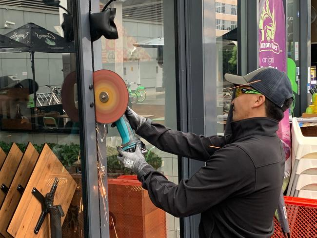 An angle grinder is used to cut through a lock on the door of Oporto on the ground floor of the structurally suspect Mascot Towers, after access from behind the commercial businesses was blocked off. Picture: Nick Hansen