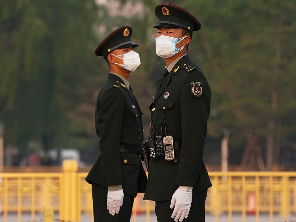 Two Chinese paramilitary policeman wears protective mask in Beijing. Picture: Getty Images