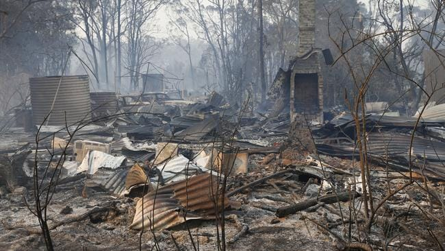 The ruins of a house smoulders on Old Bar road near Taree. Picture: AAP