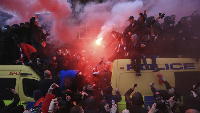 Soccer fans light flares and clamber atop Police vans before their Champions League, Semi Final First Leg soccer match at Anfield