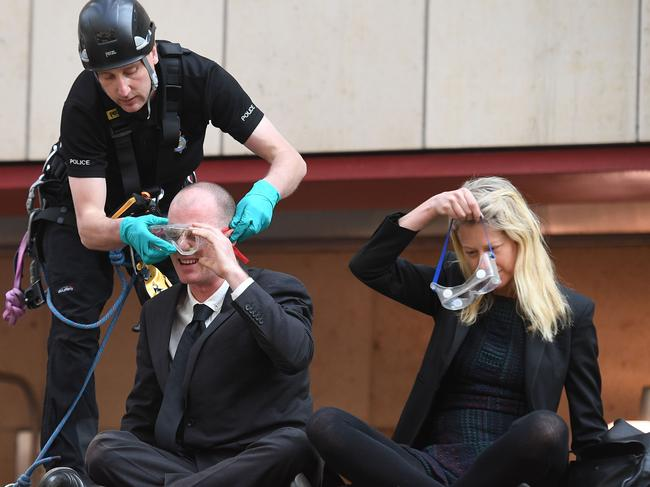 Police ask protesters to wear protective eye wear as they are removed from the roof of a DLR train at Canary Wharf station. Picture: AFP