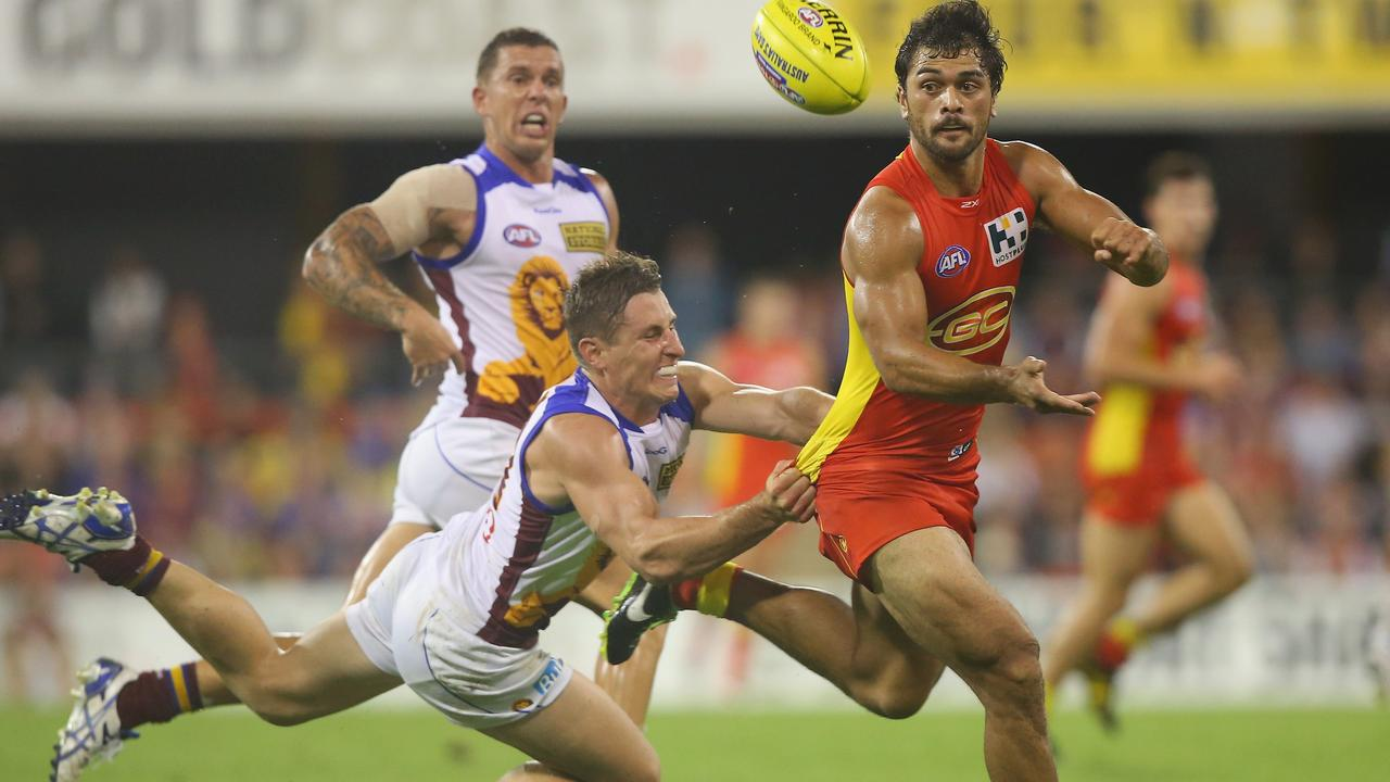 Karmichael Hunt of the Suns handballs while tackled by James Polkinghorne of the Lions.