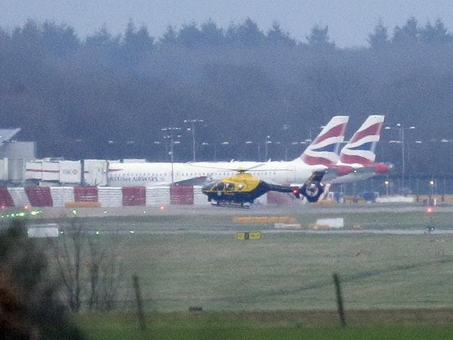 A police helicopter flies over the runway at Gatwick, as the airport remains closed with incoming flights delayed due to rogue drones. Picture: AP