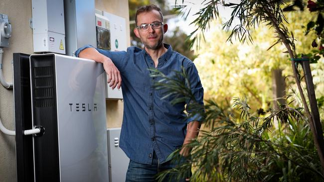Solar Quotes founder and CEO Finn Peacock alongside his Tesla battery storage unit at his house in Brighton. Photo: Kelly Barnes