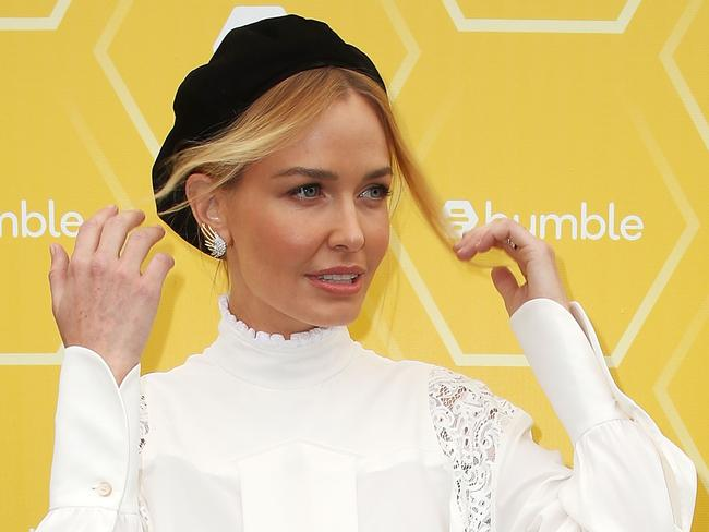 Lara Worthington fixes her hair as she poses at the Bumble Birdcage Marquee on Melbourne Cup Day at Flemington Racecourse. Picture: Scott Barbour