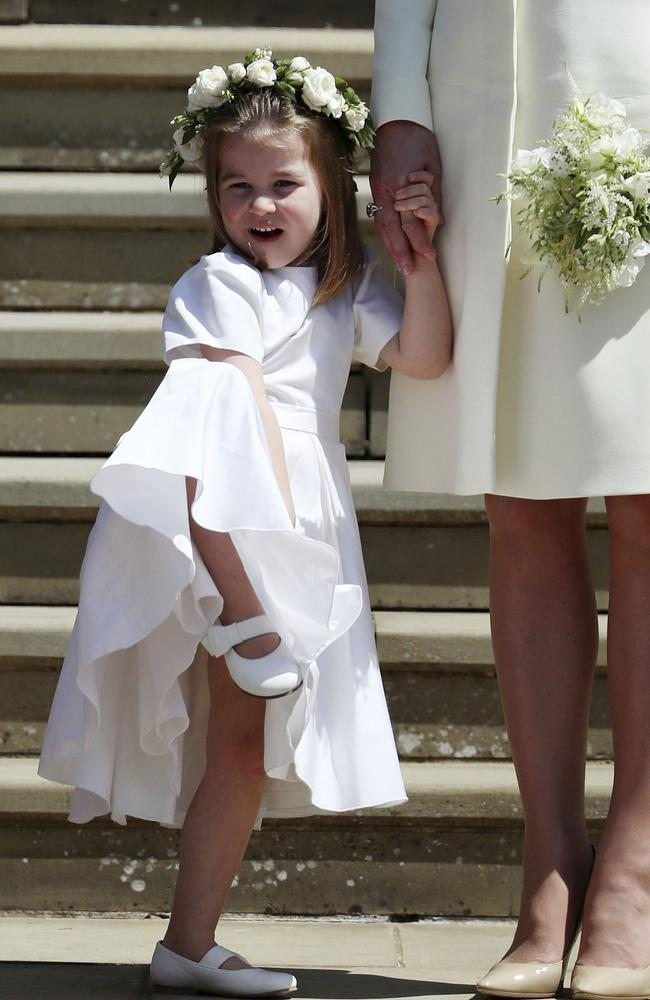 Princess Charlotte looks at Meghan Markle and Britain's Prince Harry on the steps of St George's Chapel. Picture: Jane Barlow/pool photo via AP.