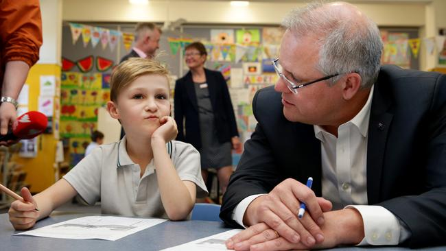 Prime Minister Scott Morrison doing some school work with year 1 student Reggie Davy, 7, during a visit to Galilee Catholic Primary School in North Bondi. Picture: Jonathan Ng