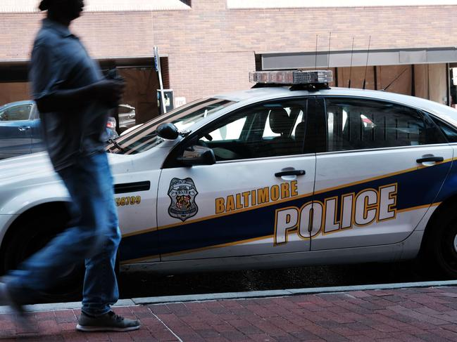 """A person walks past a police car on July 28, 2019 in Baltimore, Maryland, a city Donald Trump has called """"disgusting."""" Picture: AFP"""