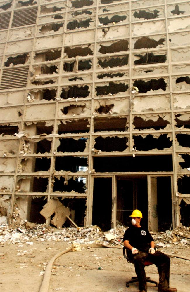 A rescuer on a break surrounded by the eerie reminder of what once was a bustling area of world commerce. Picture: Alamy