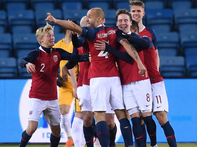 Tore Reginiussen of Norway is congratulated by team mates