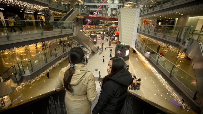 People ride an escalator in an upscale shopping mall in Beijing.
