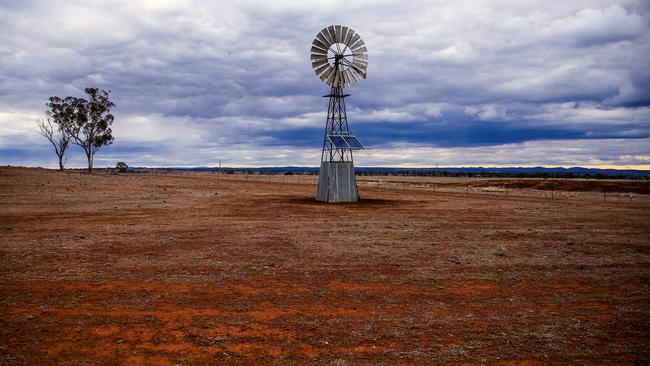 A solar-powered windmill stands in a drought-effected paddock as rain clouds move overhead on the outskirts of Dubbo, Australia. Picture: David Gray/Getty Images