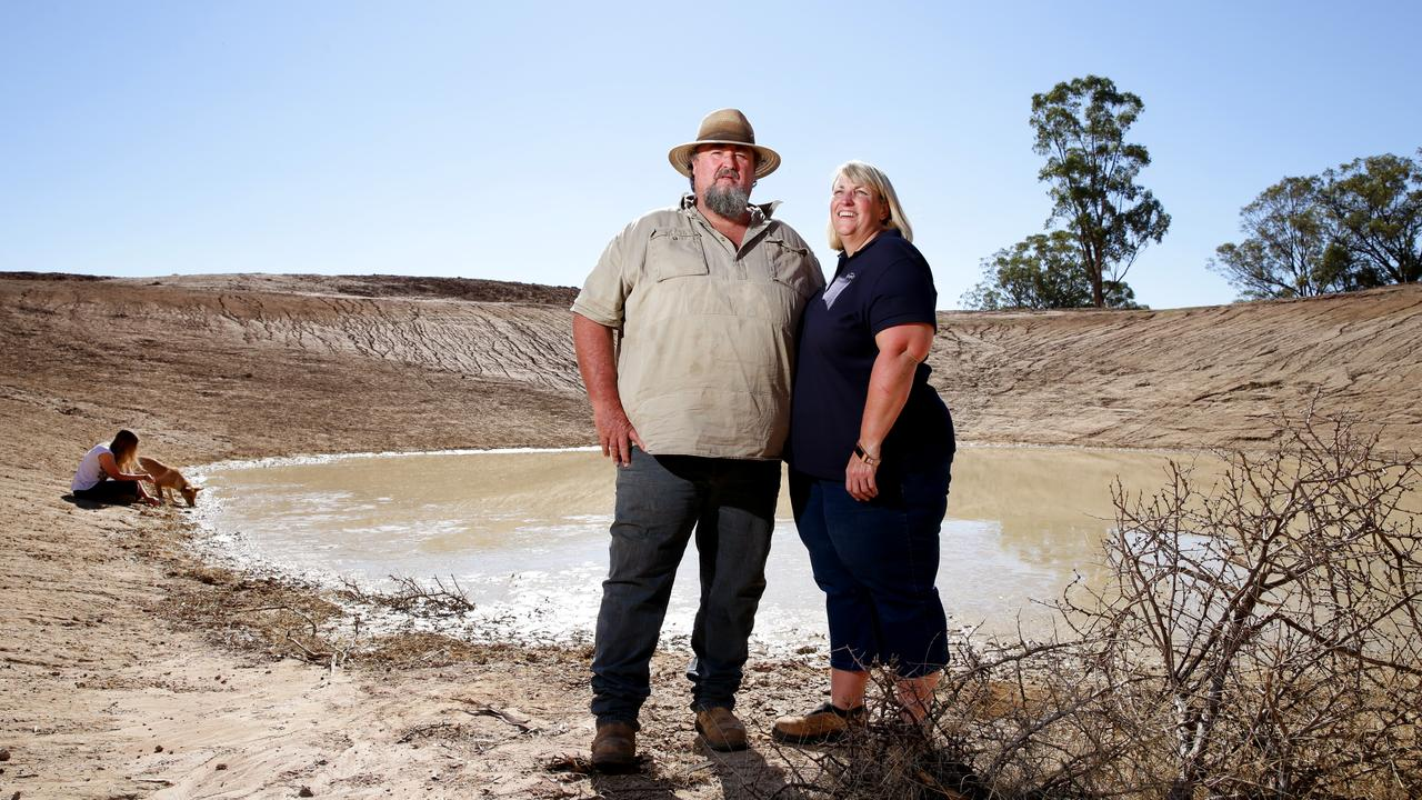 Farmers Richard and Diane Darcy with daughter Charlotte and their dog J at one of their many empty dams on their farm in Tullamore, NSW. Farmers in the worst-hit drought areas have been rationing water for several years. Picture: Jonathan Ng