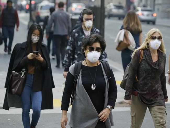 People wear masks while walking through the Financial District in the smoke-filled air in San Francisco. Picture: AP