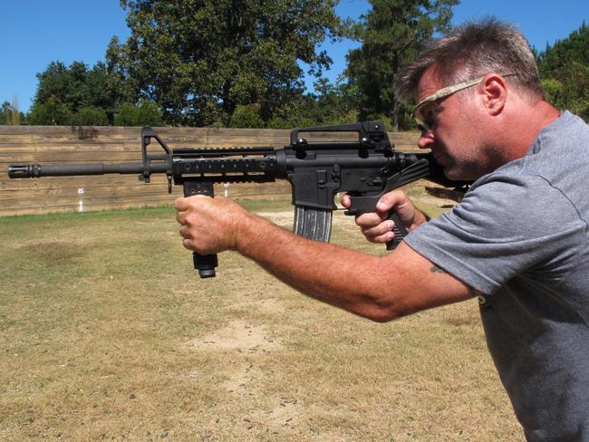 """Shooting instructor Frankie McRae aims an AR-15 rifle fitted with a """"bump stock"""" at his 37 PSR Gun Club in Bunnlevel, North Carolina. Picture: AP"""