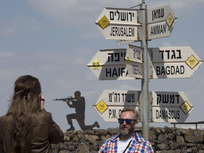 Tourists pose at an old outpost in the Israeli controlled Golan Heights, which Donald Trump has abruptly declared as undisputedly Israel's. Picture: AP Photo/Ariel Schalit