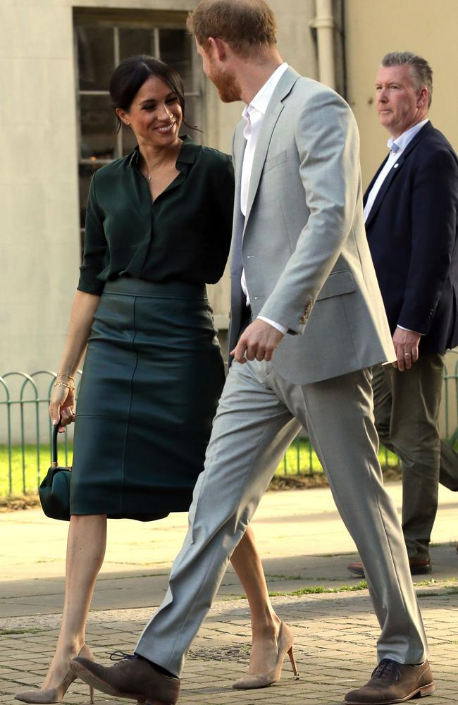 Baby clue? The Duchess wore a green leather skirt, showing a small bump, during her tour of Sussex.