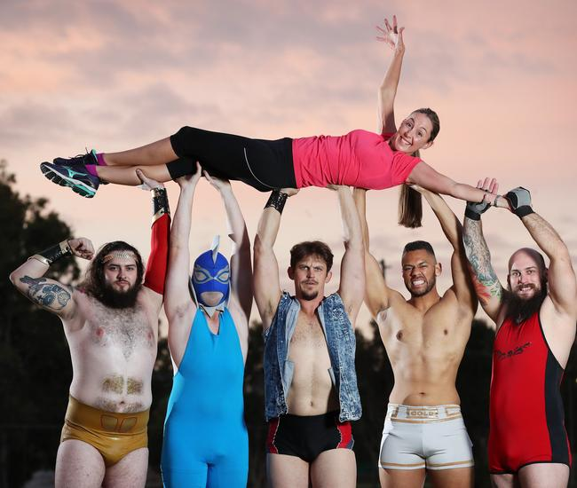 Professional wrestlers Casey Eichmann aka Adonis, Zac Hyde aka Dolph Finn, Jesse Daniels, JL Gold, and David Lewis AKA Draegan, joined by lead actor Jade Temple, star in the new TV ad for The Sunday Mail Bridge to Brisbane. Picture: Liam Kidston