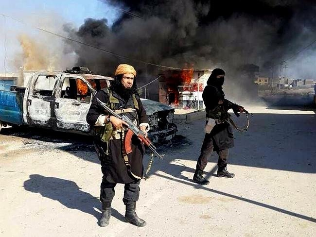 Defiant pose ... Shakir Waheib, a senior member of the al Qaeda breakaway group ISIS, left, is shown next to a burning police vehicle in Iraq's Anbar Province. Source: ISIS