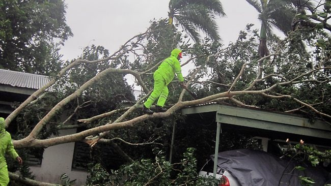 Local resident Pita Turgagaviti clears away branches from a tree that collapsed on top of a car shelter outside a house in Laucala Bay Rd near Suva as monster Cyclone Evan threatened the Pacific nation. Picture: AFP