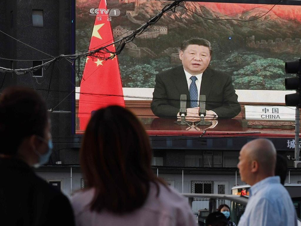 A news program shows Chinese President Xi Jinping speaking via video link to the World Health Assembly, on a giant screen beside a street in Beijing. Picture: AFP