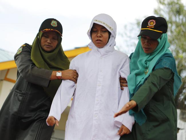 The woman being escorted by the sharia police to be whipped in front of the public. Picture: Hotli Simanjuntak/EPA