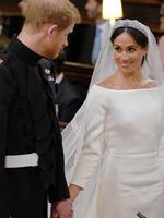 Britain's Prince Harry, Duke of Sussex (L) and Meghan Markle stand together hand in hand at the High Altar during their wedding ceremony in St George's Chapel, Windsor Castle, in Windsor, on May 19, 2018. Credit: AFP PHOTO / POOL / Dominic Lipinski