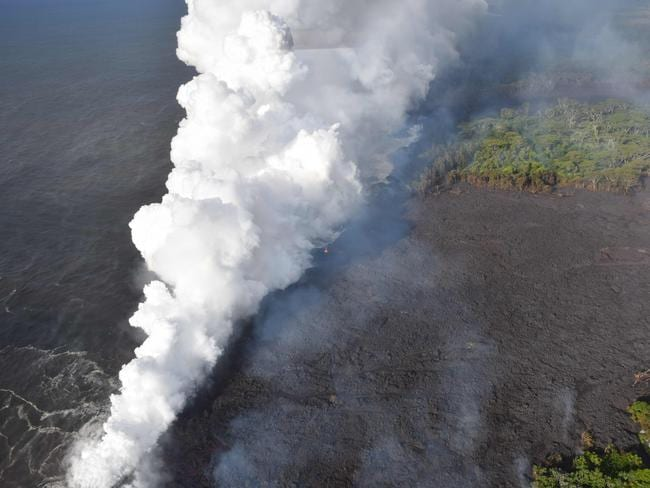 """When the hot lava flow hits the water, it produces acid fumes known as """"laze"""" — lava and haze. Picture: AFP"""
