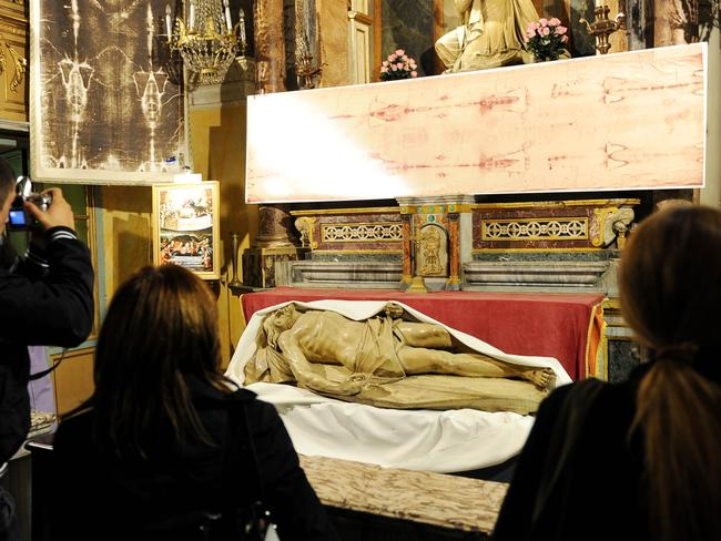 Pilgrims look at a Shroud reproduction and a Christ statue in the San Lorenzo church in central Turin on May 1, 2010. Picture: AFP Photo / Vincenzo Pinto