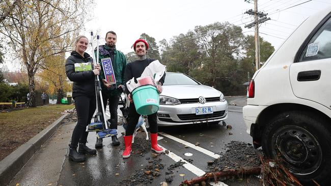 South Hobart residents Casey Morgan, left, Jason Scarr and Patrick Barnes on their way home in Degraves Street to clean up. Picture: SAM ROSEWARNE