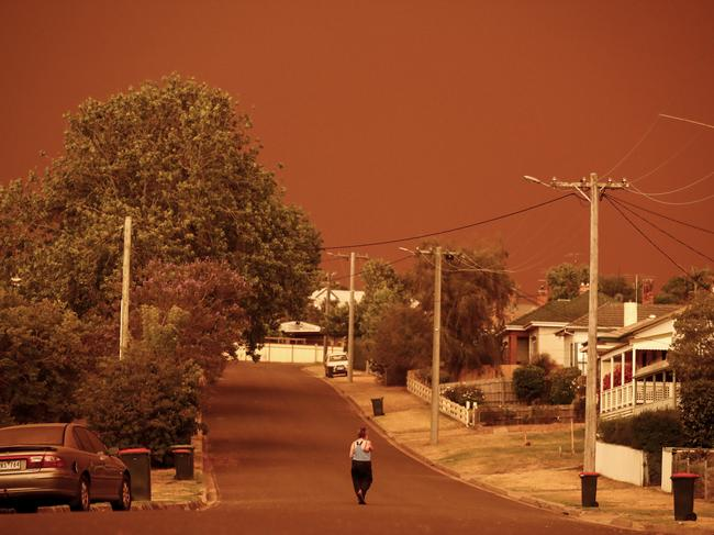 A woman from Bruthen in the East Gippsland region, walks down her street under a dark red sky. Picture: Darrian Traynor/Getty Images