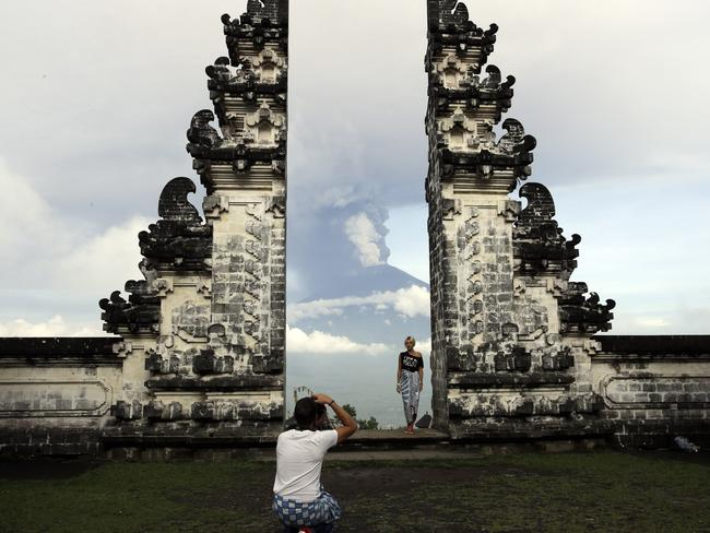 A tourist poses for a photo with Mount Agung volcano erupting as they visit a temple in Karangasem, Indonesia. Picture: AP