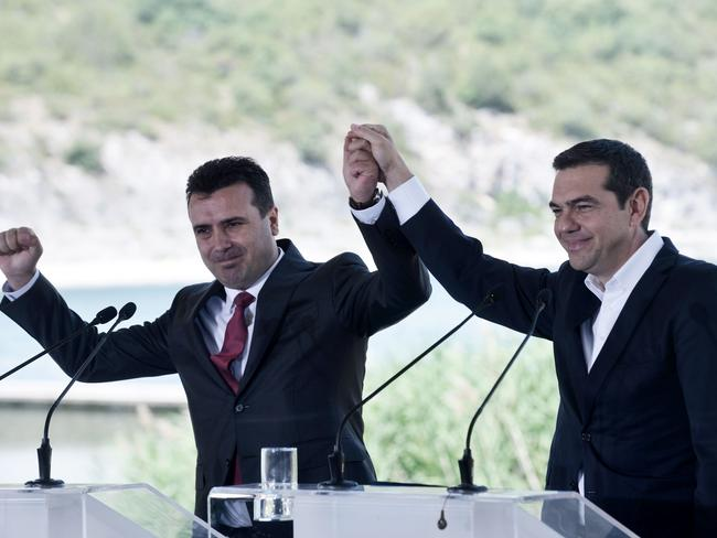 Greek Prime Minister Alexis Tsipras (R) and Macedonian Prime Minister Zoran Zaev raise their hands during the signing ceremony. Picture: AFP