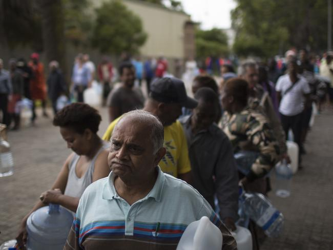 On February 2, residents wait in a queue to fill containers with water at a source for natural spring water in Cape Town. Picture: Bram Janssen