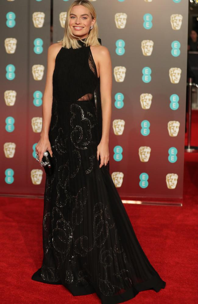 Margot Robbie poses on the red carpet upon arrival at the British Academy Film Awards.