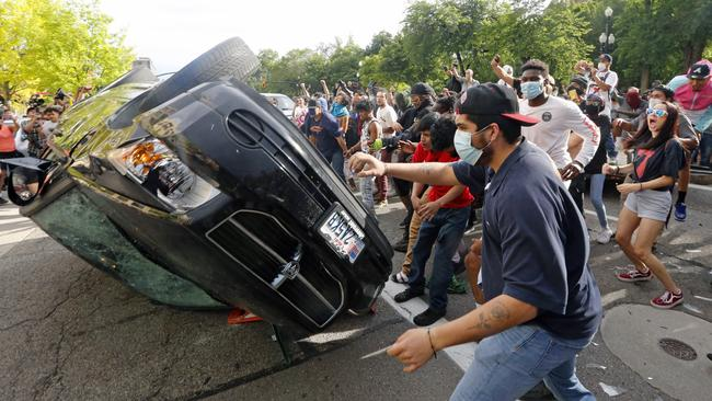 Protesters flip a car before burning it in Salt Lake City, Utah.