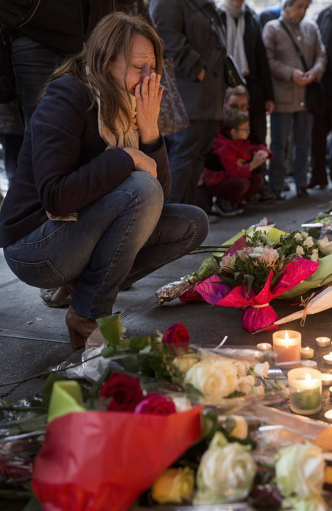 Emotional scenes ... a woman pays her respects at a floral memorial in front of La Belle Equipe cafe. Picture: Ella Pellegrini