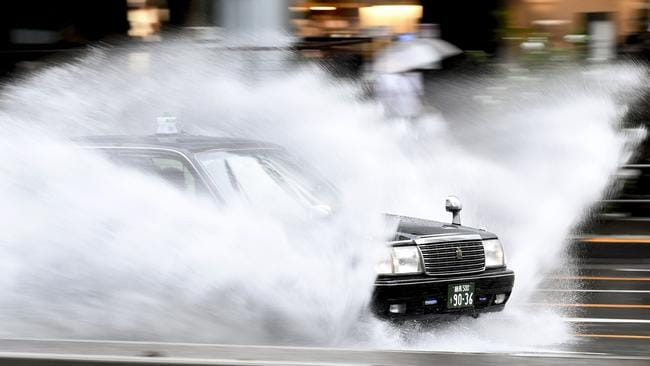 A taxi speeds through water covering a road in the Aoyama district of Tokyo. Picture: AFP