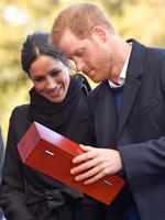 Prince Harry and his fiancée Meghan Markle open a wedding gift from Harry Smith and Megan Taylor, both from Marlborough Primary School, during their visit to Cardiff Castle on January 18, 2018 in Cardiff, Wales. Picture: Getty